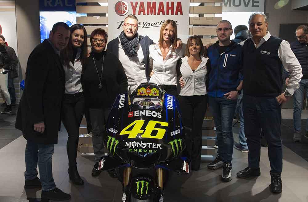 foto di otto persone del nostro staff attorno alla moto di Valentino Rossi in esposizione, ci sono quattro donne e quattro uomini